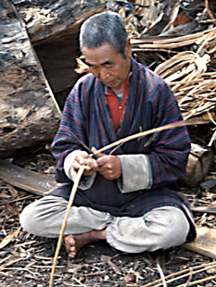 In the Himalayan kingdom of Bhutan, a man prepares fiber for weaving.